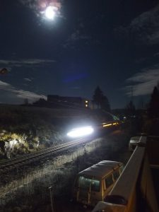 Train under a moonlit sky passing Svenseid station